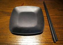 Pusty czarny talerz z chopsticks na stole Fotografia Royalty Free