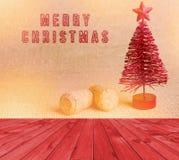 Pusty czerwony drewniany pokładu stół z Wesoło bożymi narodzeniami pisać sparkly czerwieni muśnięciem Czerwona sztuczna choinka z Fotografia Stock