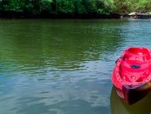 Pusty czerwony kajak unosi się na wodzie zdjęcia royalty free