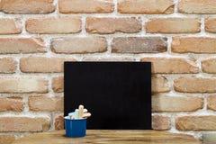 Pusty czysty blackboard kreda na drewnianym stole przy ścianą z cegieł zdjęcia stock