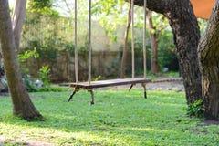 Pusty drewniany huśtawkowy obwieszenie od wielkiego drzewa z światłem słonecznym Zdjęcie Royalty Free