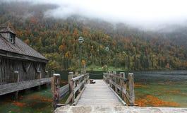 Pusty drewniany molo pięknym brzeg jeziora na mglistym mgłowym ranku Zdjęcia Royalty Free