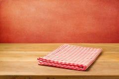 Pusty drewniany stół z sprawdzać tablecloth nad grunge czerwieni betonową ścianą. Obrazy Stock