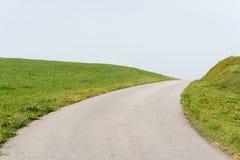 Pusty drogowy prowadzić w niebieskie niebo wzdłuż zielonych trawiastych ramion lub bulwarów zdjęcia stock