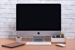 Pusty ekran iMac komputer z ipad, klawiatury, myszy i kaktusa garnkami, zdjęcie stock