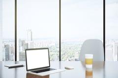 Pusty ekran laptop i papierowa filiżanka na stole z białym cha Fotografia Royalty Free