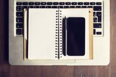 Pusty ekran smartphone na pustym dzienniczku i klawiaturze laptop Zdjęcia Stock