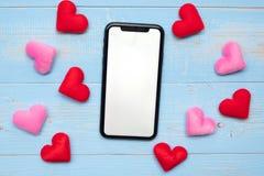 Pusty ekranu sensorowego pokaz czarny mądrze telefon z czerwieni i menchii sercami kształtuje dekorację na błękitnym drewnianym s zdjęcie stock