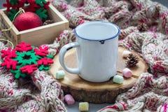Pusty emaliowy kubek, przygotowany dla gorącej czekolady z marshmallow, na drzewa cięciu, ciepły szalik na tle zdjęcie stock
