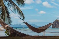 Pusty hamak z drzewkiem palmowym i łodzią na tropikalnej plaży Filipiński kurortu krajobraz Idylliczny urlopowy pojęcie zdjęcia royalty free