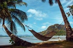 Pusty hamak z drzewkiem palmowym i łodzią na tropikalnej plaży Filipiński kurortu krajobraz Idylliczny urlopowy pojęcie obraz royalty free
