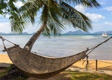 Pusty hamak z drzewkiem palmowym i łodzią na tropikalnej plaży Filipiński kurortu krajobraz Idylliczny urlopowy pojęcie zdjęcia stock