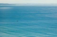 Pusty iskrzasty błękitny morze z małą łódką Obraz Royalty Free