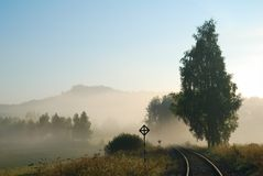 Pusty kolejowy ślad w mgłowej wsi Zdjęcia Royalty Free