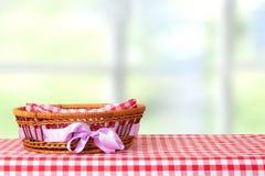 Pusty kosz z purpurowym faborkiem na czerwonym w kratkę tablecloth z obraz royalty free