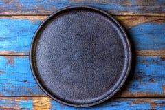 Pusty nieociosany czarny talerz nad drewnianym błękitnym tłem obrazy stock