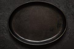 Pusty nieociosany czerni obsady żelaza talerz Na zmroku betonu tle Odgórny widok z kopii przestrzenią obraz stock