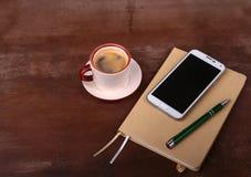 Pusty notatnik i balowy pióro z filiżanką kawy, telefon biurowy biurko pojęcia prowadzenia domu posiadanie klucza złoty sięgający Zdjęcie Royalty Free