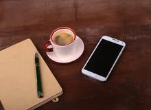 Pusty notatnik i balowy pióro z filiżanką kawy, telefon biurowy biurko pojęcia prowadzenia domu posiadanie klucza złoty sięgający Fotografia Royalty Free