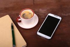 Pusty notatnik i balowy pióro z filiżanką kawy, telefon biurowy biurko pojęcia prowadzenia domu posiadanie klucza złoty sięgający Zdjęcia Stock