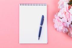 Pusty notatnik z błękitnym piórem na różowym pastelowym tle egzamin próbny, rama, szablon fotografia stock
