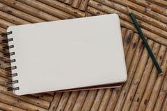 Pusty notatnik z ołówkiem na nieociosanym drewnianym stole Ślimakowaty notepad z białym papierem dla wiadomości lub rysunku obraz stock