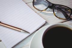 Pusty notepad z czytelniczymi szkłami i filiżanką kawy Zdjęcia Stock