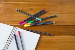 Pusty notepad z kolorowym piórem na drewnianym stole Obrazy Royalty Free