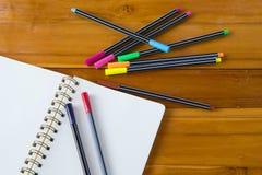 Pusty notepad z kolorowym piórem na drewnianym stole Obrazy Stock