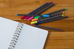 Pusty notepad z kolorowym piórem na drewnianym stole Zdjęcia Stock