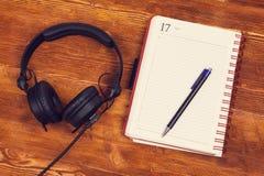Pusty notepad z piórem i hełmofony na drewnianym stołowym tle Notepad, ołówek i hełmofony, Odgórny widok insta spojrzenie Zdjęcie Stock