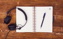 Pusty notepad z piórem i hełmofony na drewnianym stołowym tle Notepad, pióro i hełmofony, Odgórny widok insta spojrzenie Zdjęcie Stock