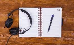 Pusty notepad z piórem i hełmofony na rocznika drewnianym stołowym tle Notepad, ołówek i hełmofony, Odgórny widok Fotografia Royalty Free