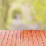Pusty perspektywiczny czerwony drewno nad zamazanymi drzewami z bokeh tłem dla produktu pokazu montażu, Obrazy Stock