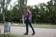Pusty plastikowa pije butelka śmieci na drogowej podłoga przy zielonym parkiem z plamy zieleni natury tłem obrazy royalty free