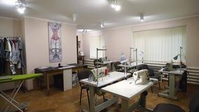Pusty projektanta atelier wnętrze z stołami i szwalnymi maszynami Wyposażający mody krawiectwa studio indoors z odziewa zdjęcie wideo
