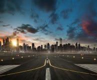 Pusty samolotowy pasa startowego kłoszenie dla nowożytnego miasta z skyscrape zdjęcie royalty free