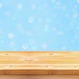 Pusty stół przed błękitną błyskotliwością zaświeca tło Zdjęcia Stock