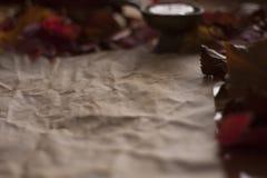 Pusty stary papier z świeczką i liśćmi na drewnianym stole obraz royalty free