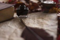 Pusty stary papier z piórkowym piórem, atrament, świeczka i biblia na drewnianym stole, fotografia royalty free