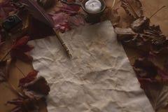 Pusty stary papier z piórkowym piórem, atrament i świeczka na drewnianym stole fotografia royalty free