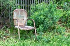 Pusty stary, wietrzejący krzesło przeciw deseczki ogrodzeniu, i greenery, starzejący się śmierci i żalu pojęcie obrazy royalty free