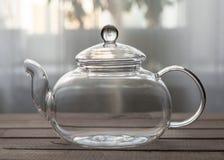 Pusty szklany teapot na drewnianym tle przed okno Zdjęcie Royalty Free