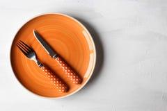 Pusty talerz i nóż, rozwidlenie na białym drewnianym tle fotografia stock