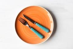 Pusty talerz i nóż, rozwidlenie na białym drewnianym tle obrazy stock