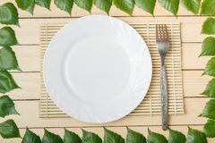 Pusty talerz na bambusowej macie z rozwidleniem, widok od wierzchołka, na drewnianym tle, obramiającym z liśćmi drzewo obraz stock