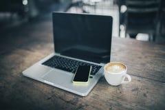 Pusty telefon komórkowy na laptopie i kawowym kubku na drewnianym stole obraz royalty free