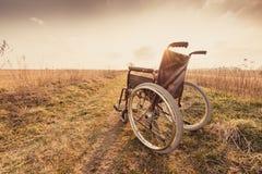 Pusty wózek inwalidzki na łące przy zmierzchem - rocznik retro wersja zdjęcie stock