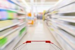 Pusty wózek na zakupy z abstrakcjonistycznym plama supermarketem Fotografia Royalty Free