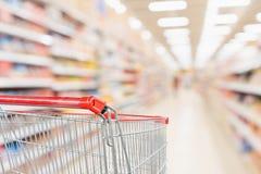 Pusty wózek na zakupy z abstrakcjonistycznymi plama supermarketa dyskontowego sklepu produktu i nawy półkami wewnętrznymi obraz royalty free